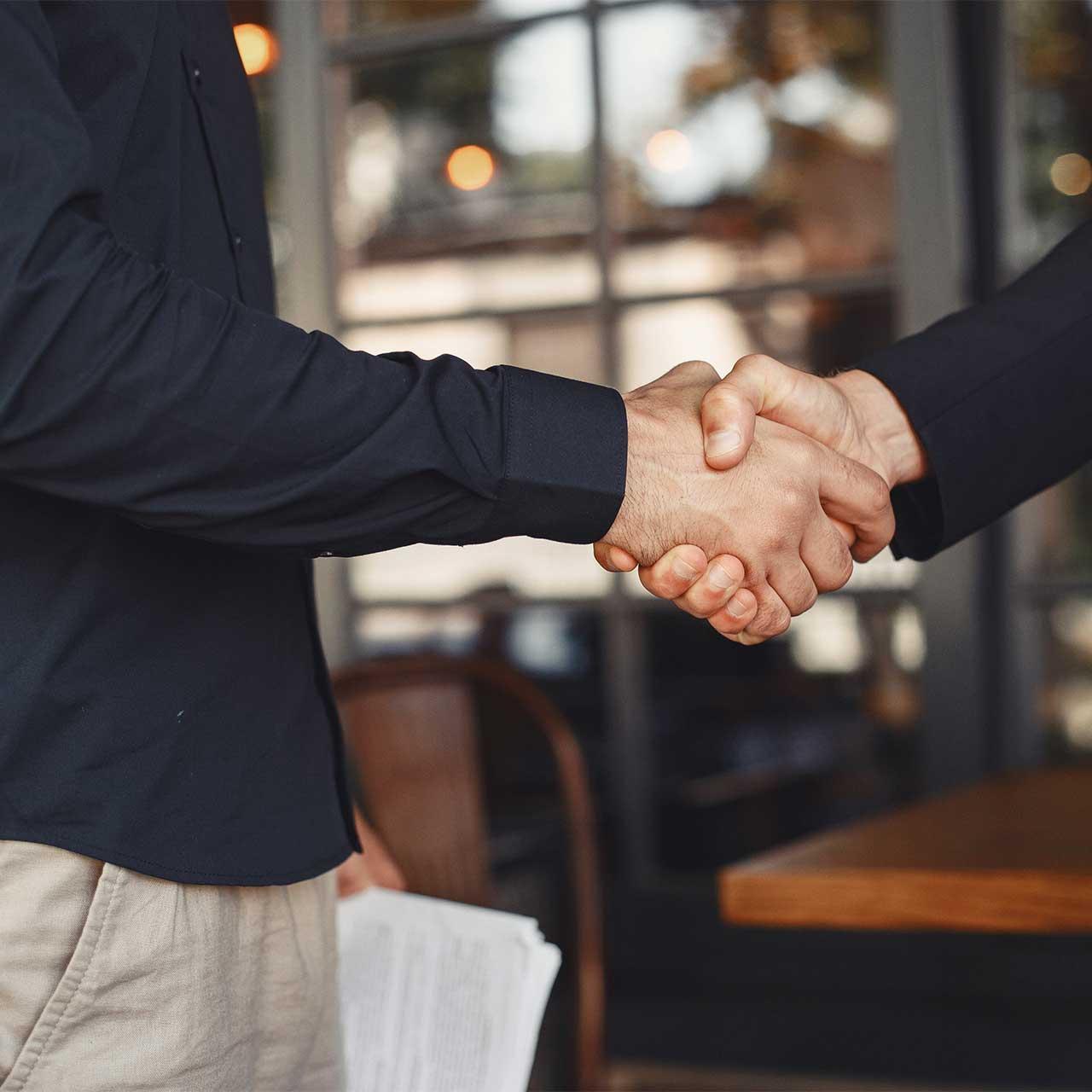 Muškarci se rukuju nakon sastanka.